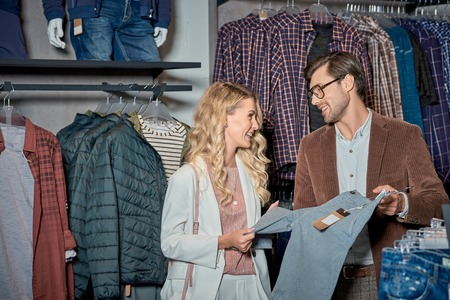Young couple smiling each other while choosing clothes in shop