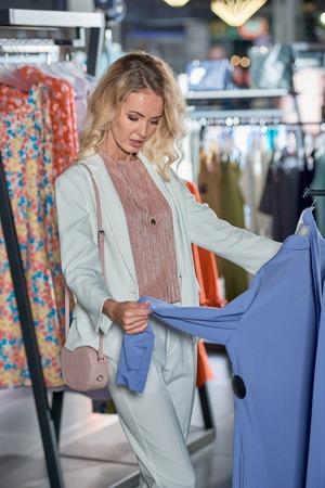 Young blonde woman choosing stylish clothes in fashion boutique Foto de archivo - 111345470
