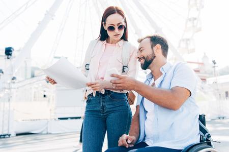 Handsome boyfriend in wheelchair using smartphone and girlfriend standing with map on street Stok Fotoğraf