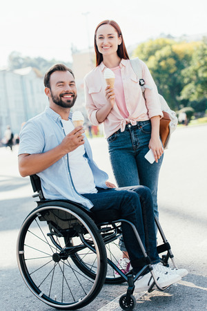 Smiling handsome boyfriend in wheelchair and girlfriend with ice cream looking at camera on street