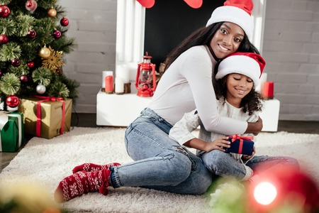 Smiling African American woman hugging little daughter with Christmas gift in decorated room at home Stock Photo