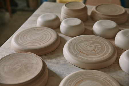 Close up view of plates at table in pottery studio