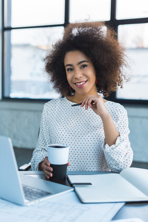 African American businesswoman holding cup of coffee and looking at camera in office
