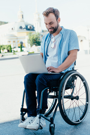 Handsome man in wheelchair using laptop on street