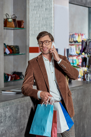 Smiling young man in eyeglasses holding shopping bags and talking by smartphone while shopping in mall Foto de archivo - 111346214