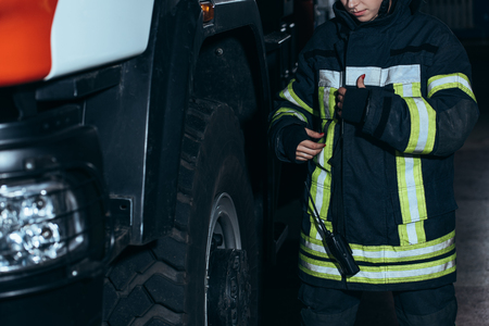 Cropped shot of female firefighter in protective uniform with portable radio set at fire department