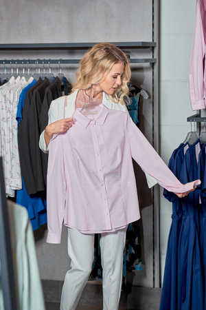 Beautiful young woman holding hanger with stylish shirt in boutique Foto de archivo - 111346471