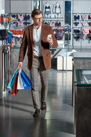 Handsome young man in eyeglasses holding paper bags and using smartphone in shop Foto de archivo - 111346311
