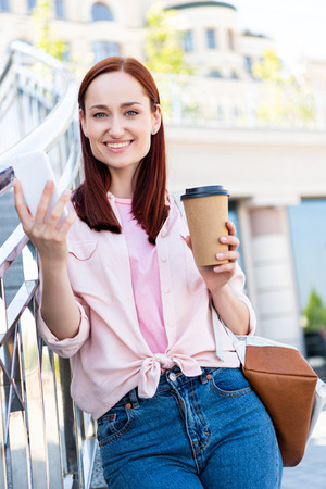 Attractive red hair woman in pink shirt holding smartphone with disposable coffee cup and looking at camera on street