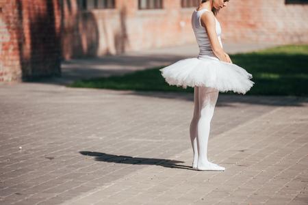 Cropped shot of ballerina in white tutu skirt standing on street Imagens