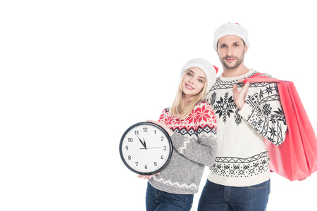 Portrait of young couple in Santa Claus hats with clock and shopping bags isolated on white background