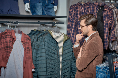 Handsome young man with hand on chin looking at stylish clothes in boutique Foto de archivo - 111346633