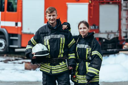Portrait of firefighters in fireproof uniform standing on street with fire truck behind Foto de archivo