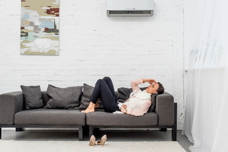 Side view of diseased young woman lying on couch under air condition at home