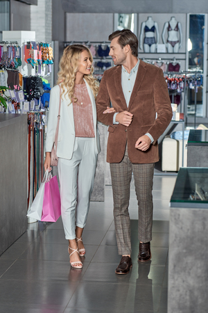 Stylish young couple with shopping bags smiling each other in boutique Foto de archivo - 111389727