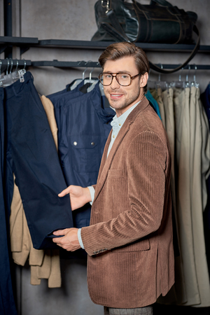 Handsome young man in eyeglasses choosing clothes and smiling at camera in shop Foto de archivo - 111389729