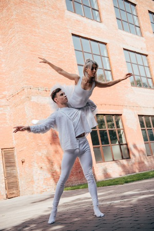 Low angle view of young ballet dancers in white clothes dancing on street Foto de archivo - 111390548