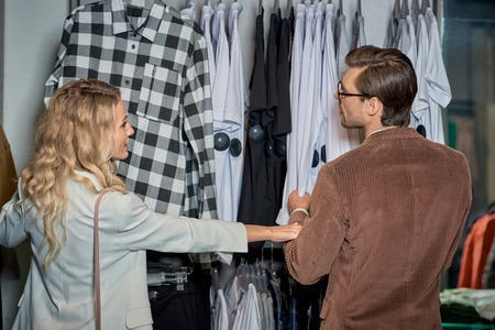 Back view of young couple choosing stylish clothes together in boutique Foto de archivo - 111390552