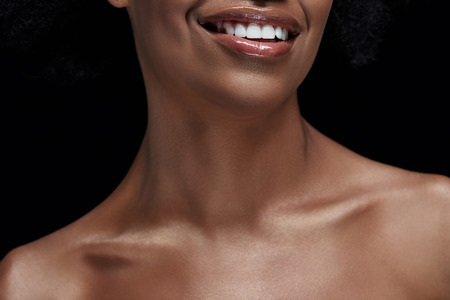Cropped shot of smiling African American woman with bare shoulders isolated on black background
