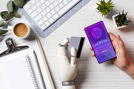 Partial view of businessman with prosthesis arm holding credit card and using smartphone with shopping on screen at table in office Stock Photo
