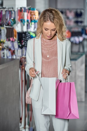 Young woman looking into shopping bag in store Foto de archivo - 111390422