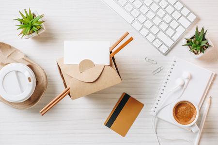 Vista superior de la tarjeta de visita vacía, tarjeta de crédito, caja de wok, taza de café de papel en la mesa de la oficina
