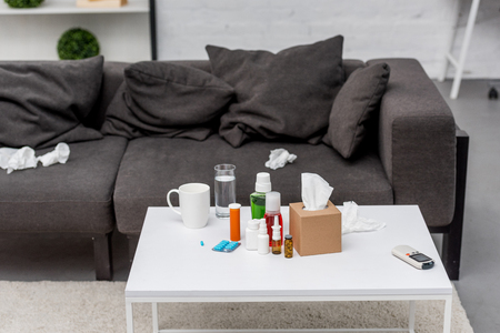 Table with various medicines and couch at living room