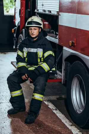 Male firefighter in uniform and helmet at fire truck at fire department