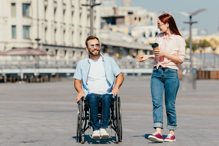 Smiling handsome boyfriend in wheelchair and girlfriend with coffee to go having walk on street Stock Photo
