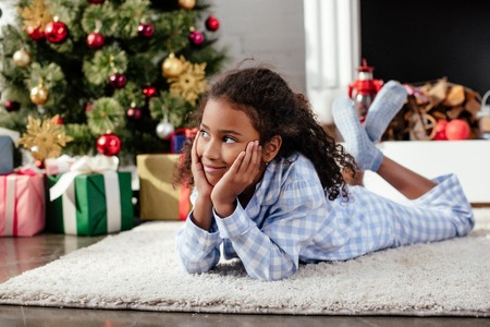 Adorable African American child in pajamas lying on floor and looking away at home, Christmas concept