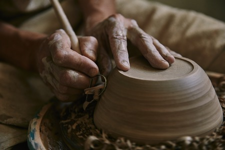 Selective focus of professional potter decorating clay pot at workshop