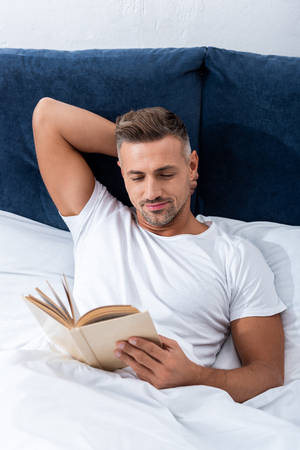 High angle view of man reading book while laying in bed during morning time at home