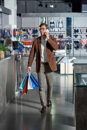 Handsome smiling man in eyeglasses holding paper bags and talking by smartphone in shop Foto de archivo - 111390722