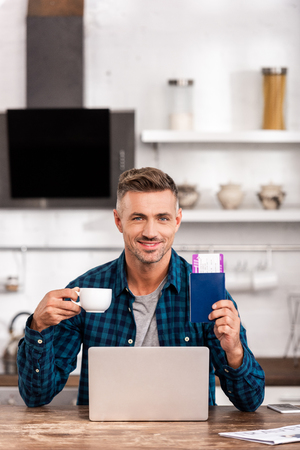 Handsome smiling man holding cup of coffee and passport with boarding pass while using laptop at home