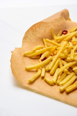 Delicious french fries with spicy peppers on parchment paper on white background