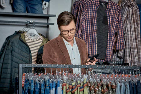 Handsome man in eyeglasses holding smartphone and choosing fashionable clothes in shop Foto de archivo - 111390872