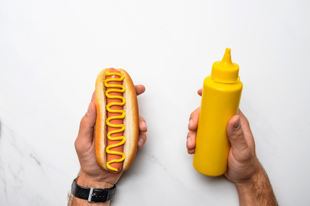 Cropped shot of man holding tasty hot dog with mustard on white marble surface