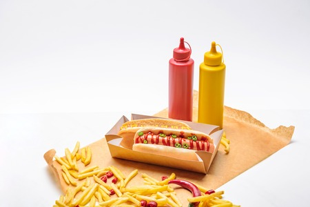 Close-up shot of hot dogs with french fries, mustard and ketchup on paper on white surface background Foto de archivo - 111391017