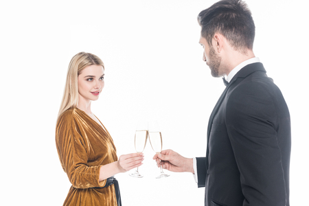 Fashionable couple clinking glasses of champagne isolated on white background