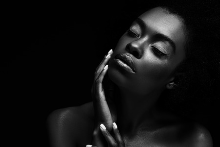 Black and white photo of beautiful African American woman isolated on black background 写真素材