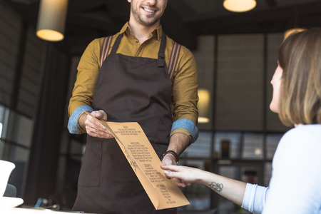 Cropped shot of smiling waiter showing menu list to female customer in cafe