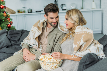 Happy young couple with popcorn watching at each other on couch at home