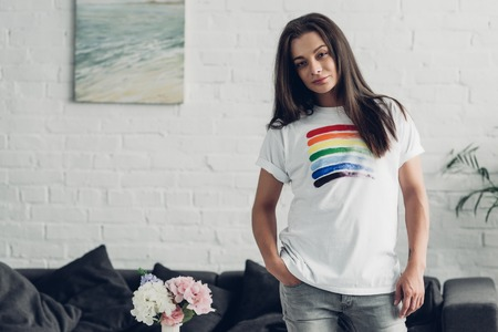 Young man in white t-shirt with pride flag looking at camera at home