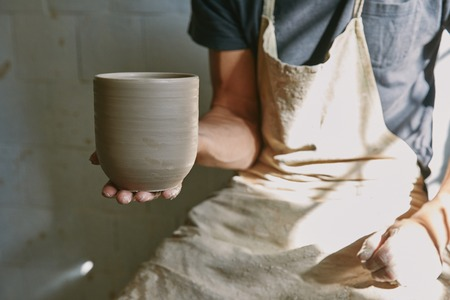 Cropped image of professional potter in apron holding clay pot at workshop Stok Fotoğraf