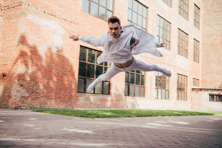 Low angle view of young ballet dancer in jump on city street Foto de archivo - 111391152
