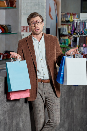 Uncertain man in eyeglasses holding shopping bags and looking at camera in store Foto de archivo - 111391153