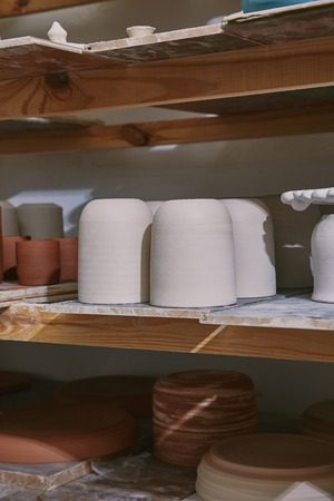 Selective focus of ceramic bowls and dishes on wooden shelves at pottery studio