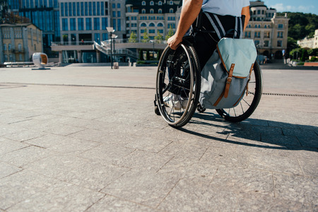 Cropped image of man using wheelchair with bag in city Stock Photo