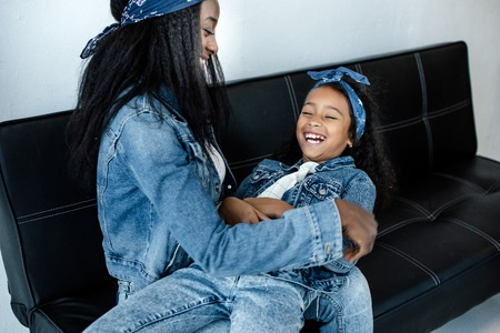 Happy African American woman having fun with daughter in similar clothing on sofa at home 스톡 콘텐츠