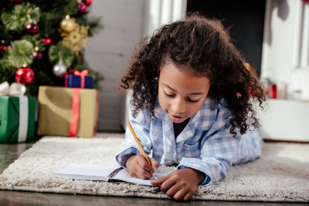 Adorable African American child in pajamas lying on floor and writing something to notebook at home, Christmas concept